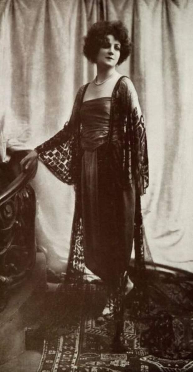 Платье черного цвета отлично подчеркивает фигуру, а прозрачная накидка добавляет таинственности.