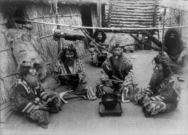 Шесть айнов в традиционных нарядах сидят у чаши. айны, история, народ, фотография