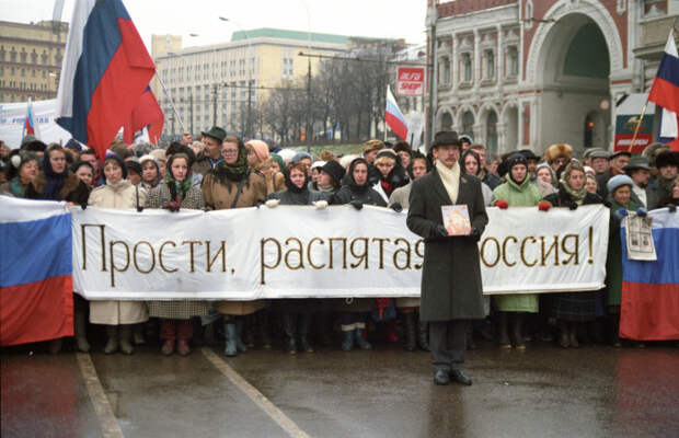 """Люди несущие баннер с надписью """"Прости, распятая Россия!""""."""