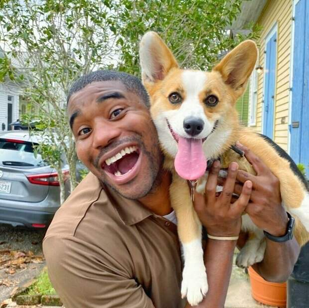 Веселый курьер фотографируется скаждой собакой, которую встречает