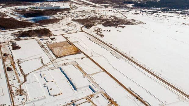 На фото площадки будущего комплекса на дальнем плане виден строящийся трубопрокатный цех Выксунского завода ОМК по выпуску бесшовных труб, запуск — в 2022 году