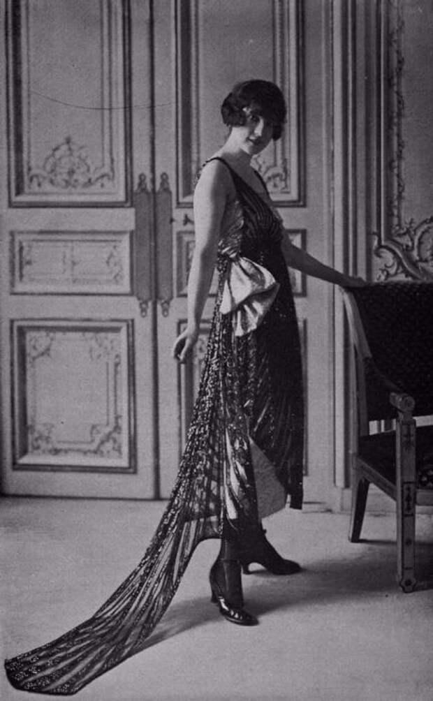 Золотисто-черное платье на лямках с накидкой и бантиком сбоку придают модели совершенства.