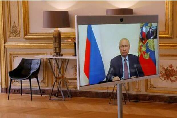 Russian President Vladimir Putin appears on a television screen during a video conference with French President Emmanuel Macron at the Elysee Palace in Paris, France, June 26, 2020. Michel Euler/Pool via REUTERS