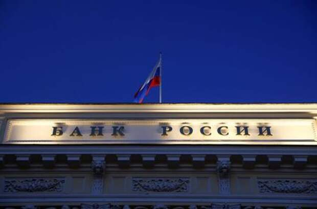 A Russian state flag flies over the Central Bank headquarters in Moscow, Russia March 29, 2021. A sign reads: