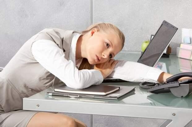 блондинка лежит головой на столе в офисе