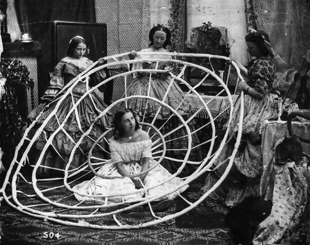 Женщина ждет, пока работницы лондонского ателье не завершат собирать обручи ее кринолина. 1860 год.