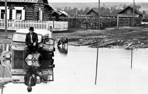 Черно-белое полотно с изображением машины и водителя, застрявшей посреди проселочной дороги в огромной луже.