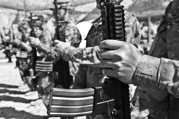 На фото изображены солдаты с автоматами в руках.
