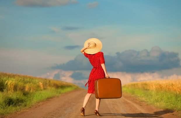 девушка с чемоданом на дороге