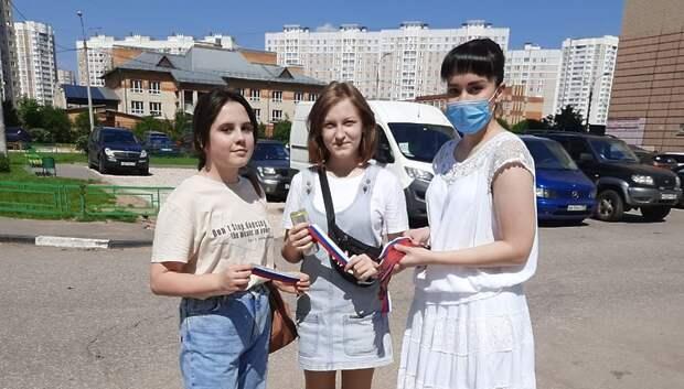 Прохожим в Подольске раздали ленты цветов флага России