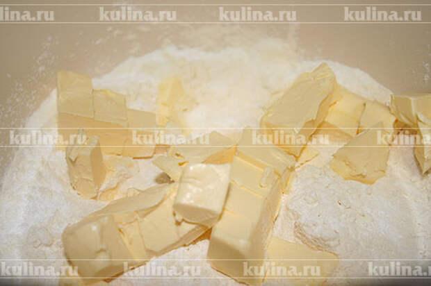 В миске смешать сахарную пудру с кусочками сливочного масла, растереть массу до состояния рыхлой смеси.