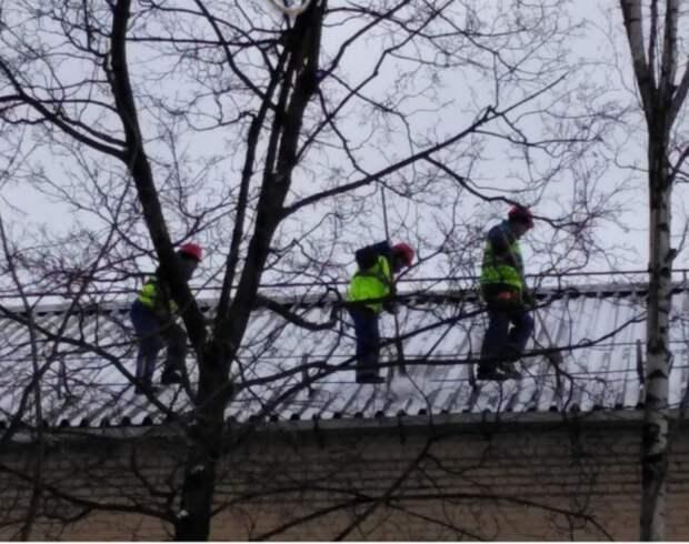В Лианозове в условиях снегопада очищают скатные крыши