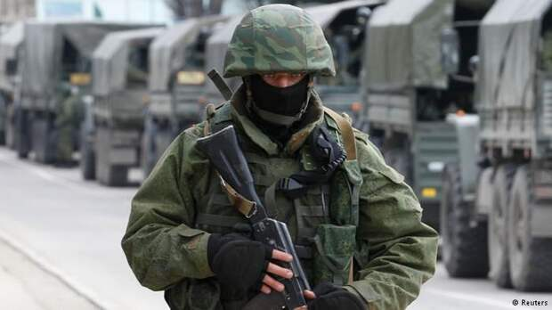 Российский солдат на фоне колонны военных грузовиков