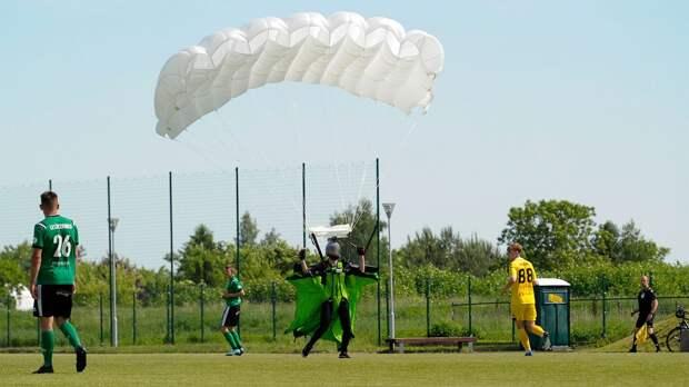 В Польше прямо во время матча на поле приземлился парашютист. Судья показал экстремалу желтую карточку: видео