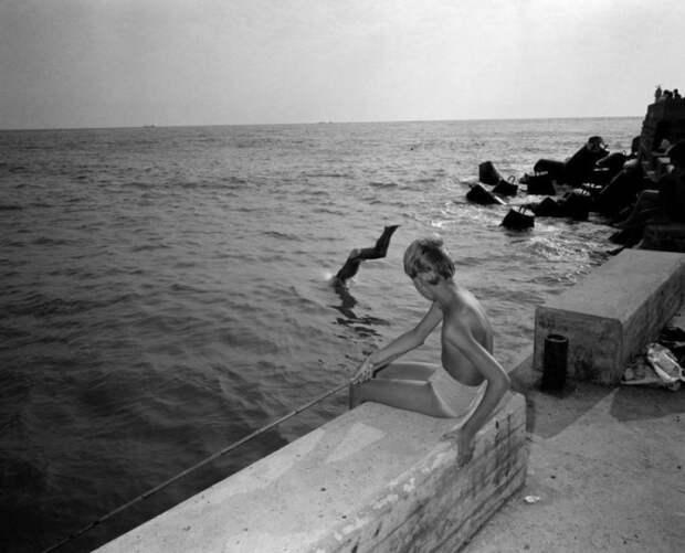 Мальчишка рыбачит на пирсе.