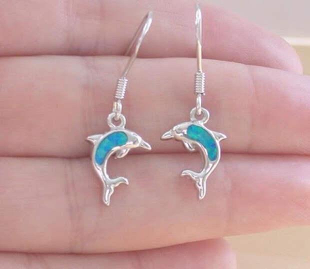 серьги-дельфины на женской ладони