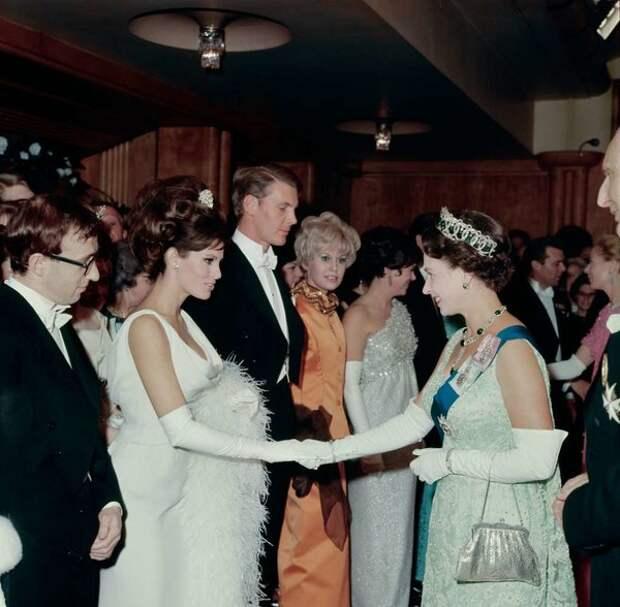 Королева экрана Рэкел Уэлч и королева Великобритании Елизавета II. Рядом Вуди Ален.