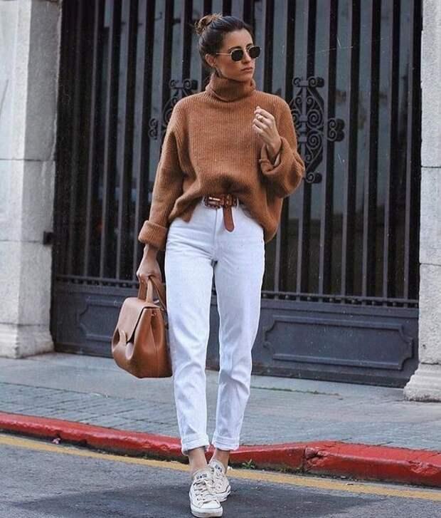 Девушка в прямых белых джинсах, коричневый свитер и кроссовки