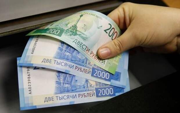 A woman holds new 200 and 2,000 rouble banknotes in a bank in Moscow, Russia November 21, 2017. REUTERS/Maxim Shemetov