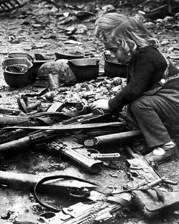 Девочка играет с оружием на улице Берлина. Май 1945 года.