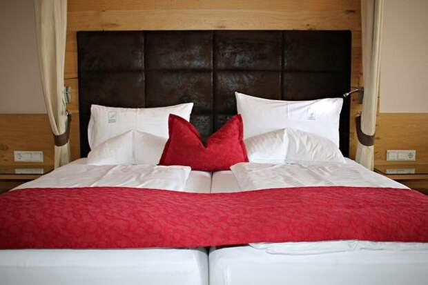 двуспальная кровать с белым постельным и красным покрывалом