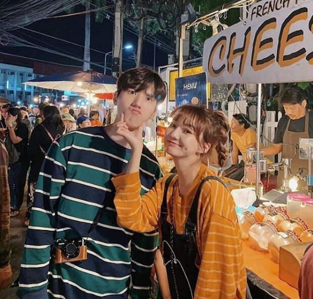 молодая корейская пара в полосатых футболках