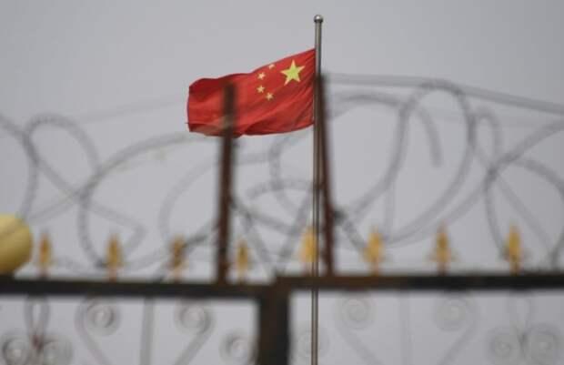 Китайский флаг за колючей проволокой на жилом комплексе в Синьцзяне