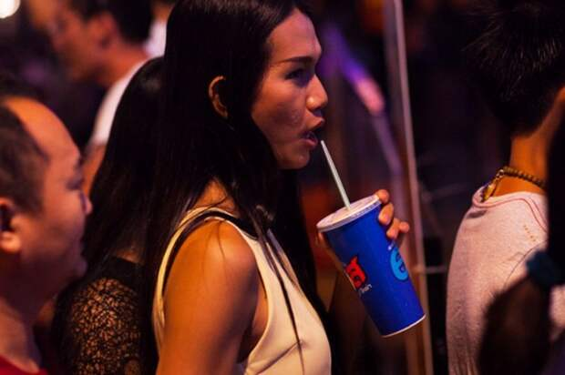Bangkok, Thailand - December 31, 2015: A young thai transgender is standing in sidewalk in Ratchada and is drinking a Pepsi. Around are many  people. Scene is in new years night close to Ratchada and mall Street23.