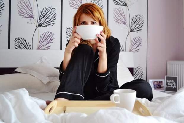 девушка сидит в постели с чашкой в руках