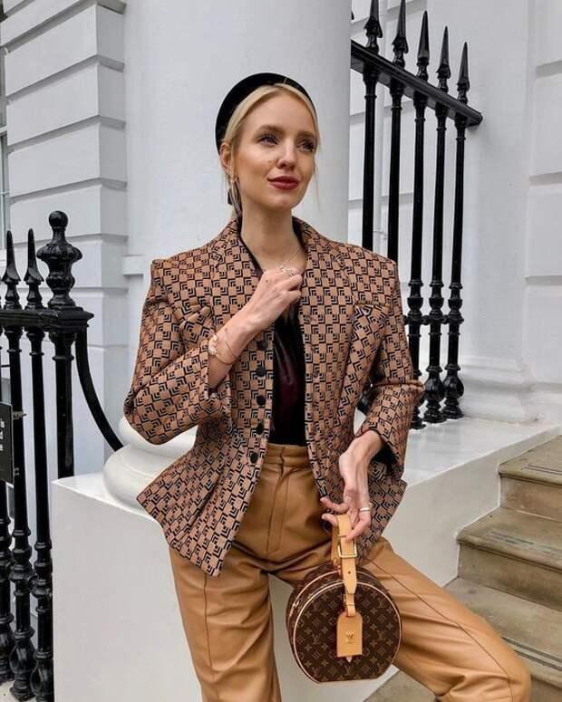 Девушка в коричневых кожаных брюках, жакет с принтом, круглая сумочка и черный бархатный ободок