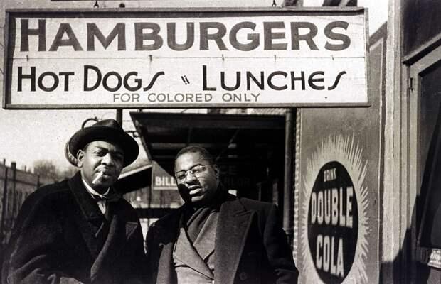 Два негра перед входом в кафе с надписью Гамбургеры и хот-доги. Только для цветных