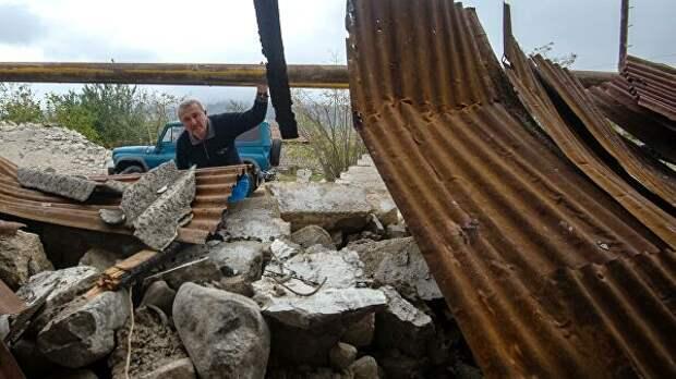 Мужчина у хозяйственной постройки, разрушенной в результате обстрела общины Иванян Нагорного Карабаха