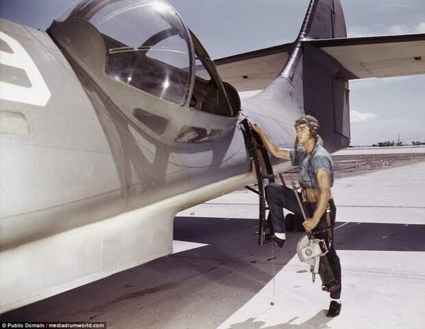 Aviation Ordnance Mate Jesse Rhodes Waller prepares to install a .30-caliber machine gun in a Navy PBY plane
