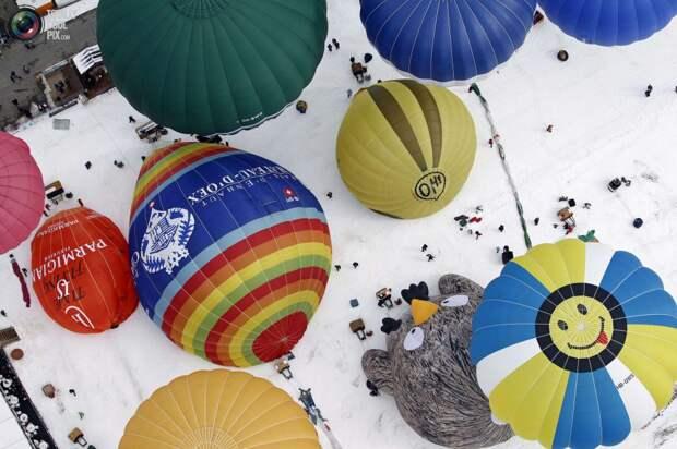 Воздушные шары всех форм и размеров готовятся к взлёту на 37-й Международной неделе воздухоплавания в Шато-д'О, Швейцария.