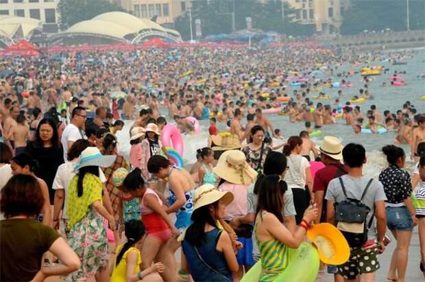 Китайцам в своей стране становится уже тесно. На фото: отдыхающие на пляже г. Циндао.