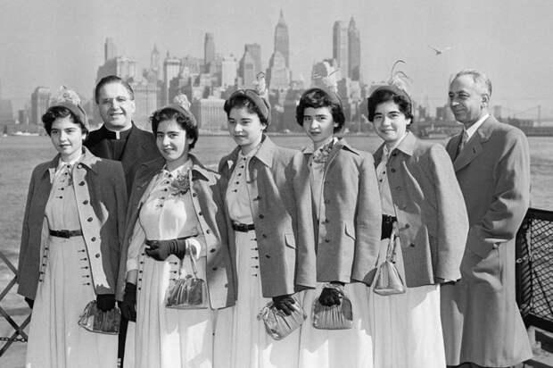 Взрослые сёстры-пятерняшки Дионн со своим отцом и священником.