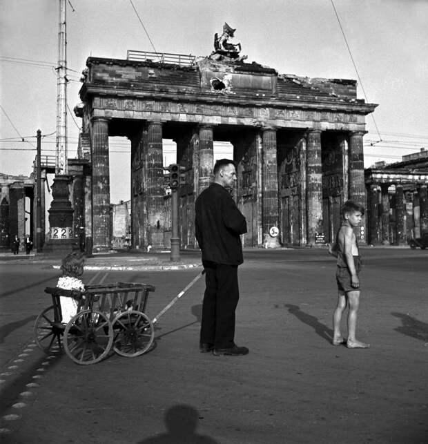 Германия, Берлин, 1947 год - Мужчина со своими детьми бродит возле Бранденбургских ворот