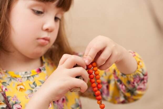 Девочка делает бусы из ягод