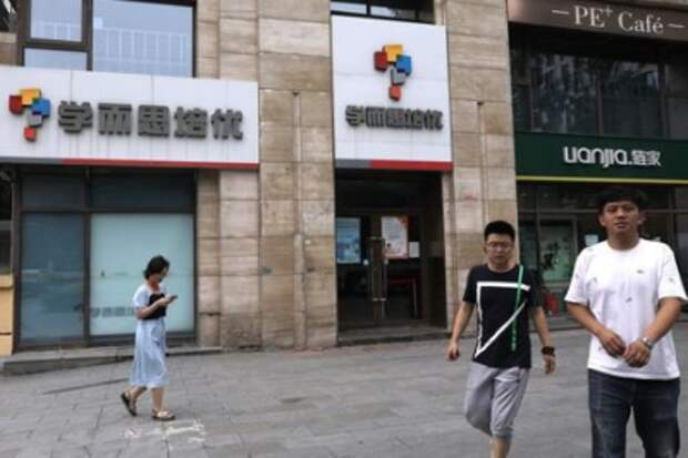 People walk past a Xueersi outlet, a private educational services provider owned by TAL Education Group, in Beijing, China July 26, 2021. REUTERS/Tingshu Wang