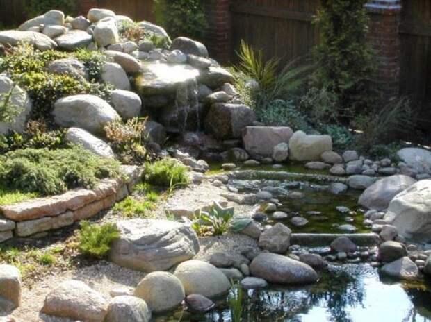 Пример альпинария в сочетании с прудом и водопадом. Обратите внимание на округлённую форму камней