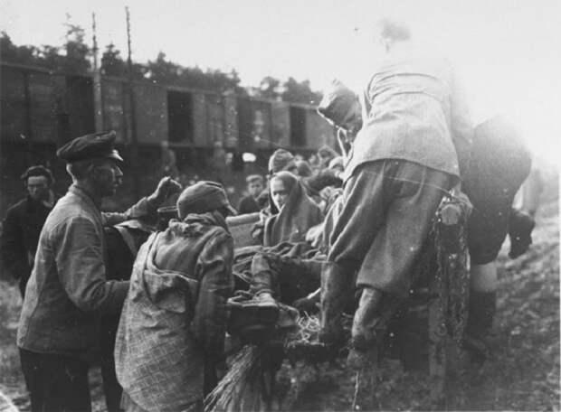 Солдат помогает обессиленному военнопленному подняться в кузов машины.