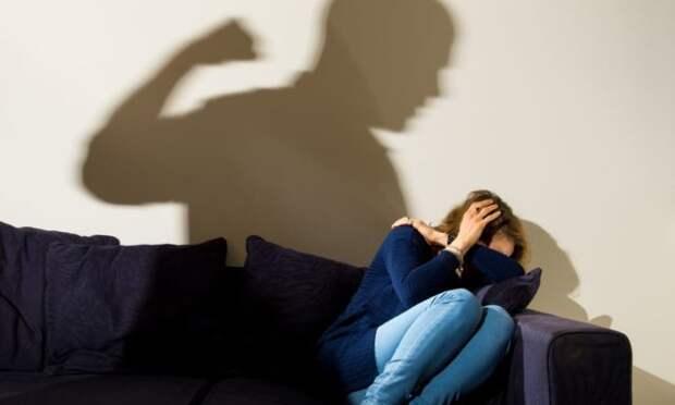 женщина сидит на диване, закрыв голову руками
