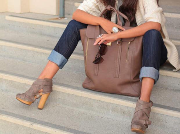 девушка сидит на ступеньках с большой коричневой сумкой