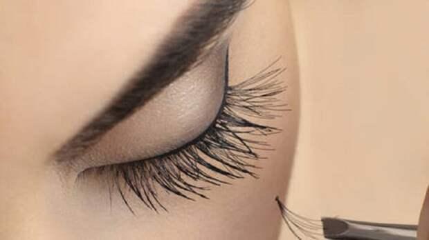 девушка клеит пучки ресниц на глаза