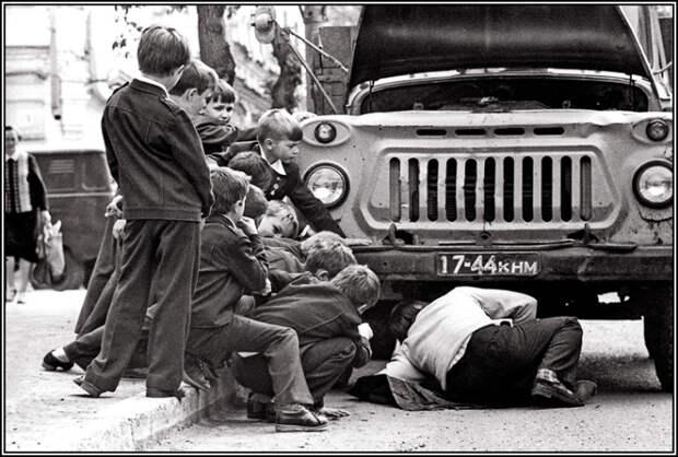 Группа подростков рядом с мужчиной, ремонтирующим автомобиль.