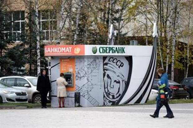 Women stand at a Sberbank ATM decorated with a picture of cosmonaut Yuri Gagarin in Star City near Moscow, Russia, October 21, 2020. Picture taken October 21, 2020. To match Special Report HEALTH-CORONAVIRUS/RUSSIA-STARCITY REUTERS/Evgenia Novozhenina