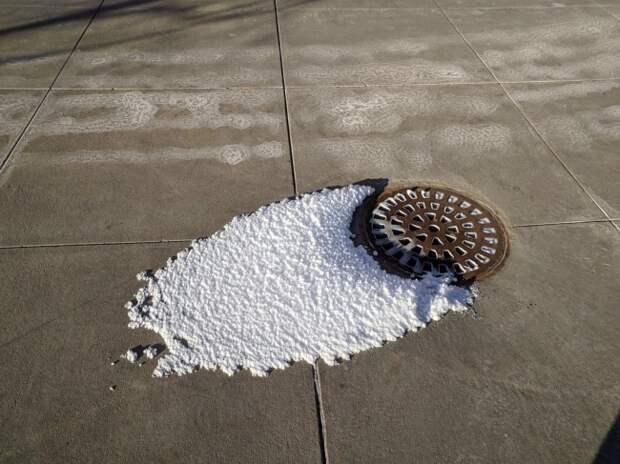 Пар из канализационной решетки превратился в снег из-за мороза.