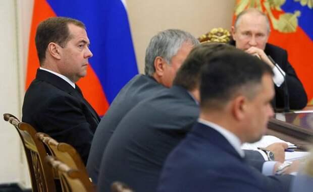 На фото: президент РФ Владимир Путин (на втором плане) и премьер-министр РФ Дмитрий Медведев (слева) во время совещания