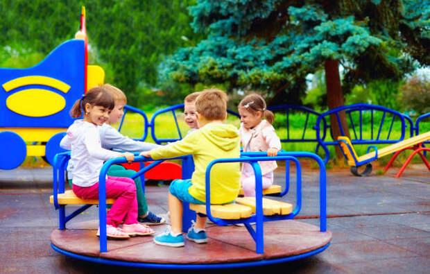 группа счастливых детей весело провести время на кольцевой развязке на детской площадке - качели на детской площадке стоковые фото и изображения