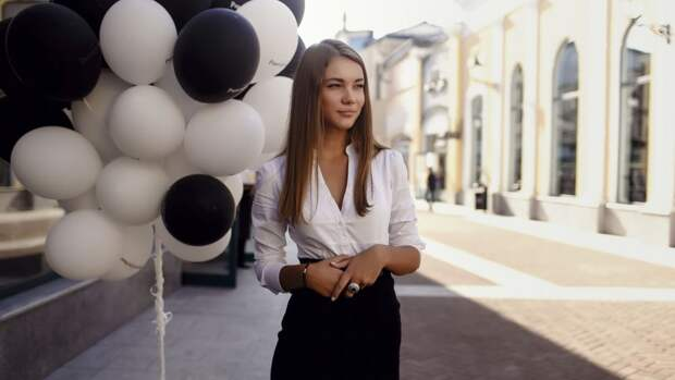 Обои Девушка в блузе и юбке на улице, рядом черно-белые надувные ...